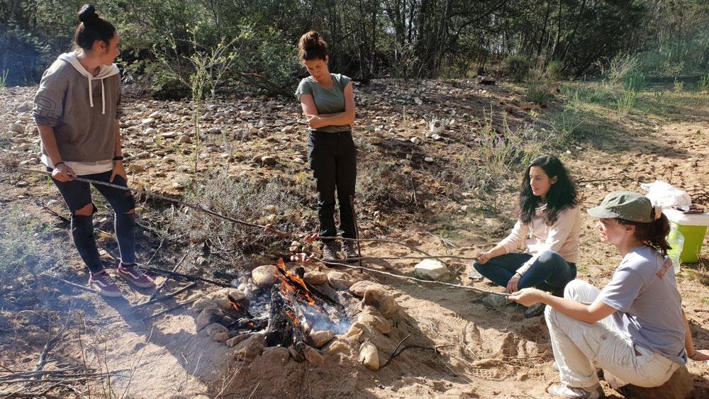4 Reisende sitzen um ein Lagerfeuer im afrikanischen Busch