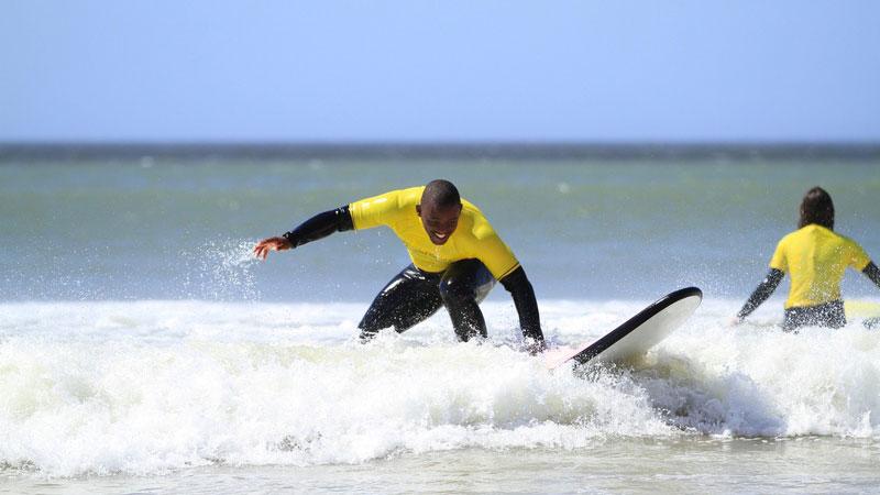 cara de pé em uma prancha de surf durante as aulas de surf em J-Bay