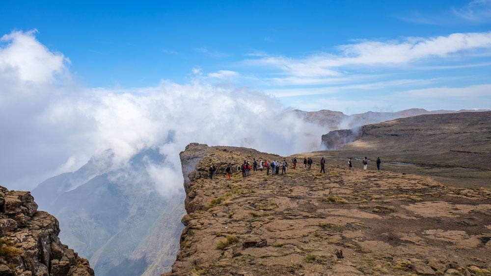 Reisegruppe wandert auf dem Amphitheater in den Drakensbergen