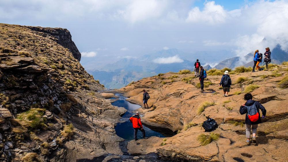 travellers hiking in the drakensberg at tugela falls