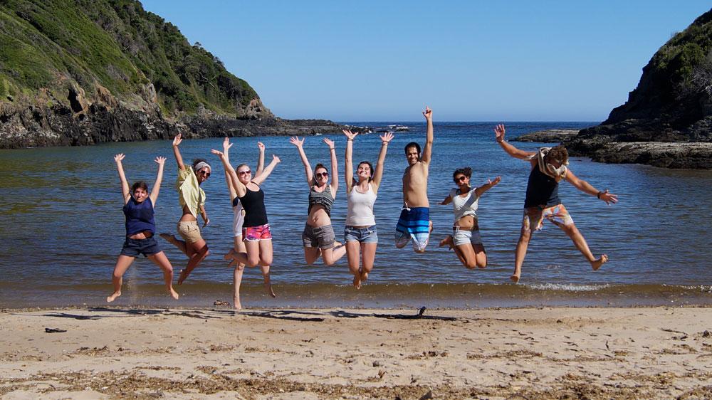 Springende Reisegruppe am Strand in einer Bucht